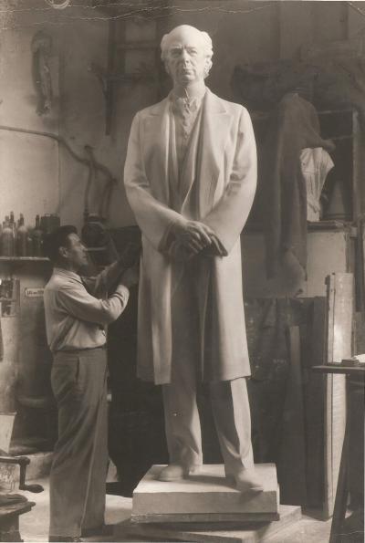 Photographie d'Émile Brunet travaillant sur une grande sculpture dans un atelier.