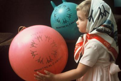 Petite fille avec foulard Expo 67 et deux ballons avec le logo d'Expo 67