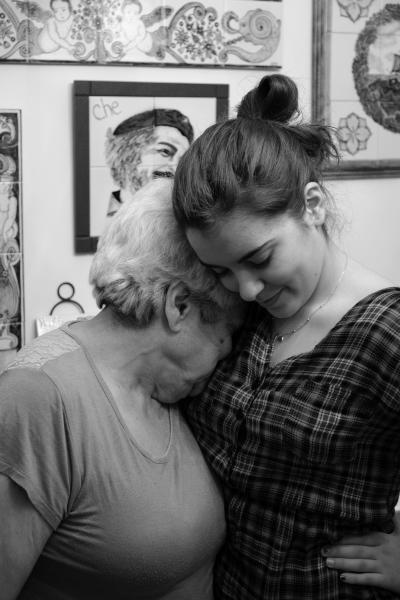 Photo en noir et blanc montrant une grand-mère et sa petite-fille enlacées en plan rapproché. Le visage de la grand-mère est caché dans l'épaule de sa petite-fille.
