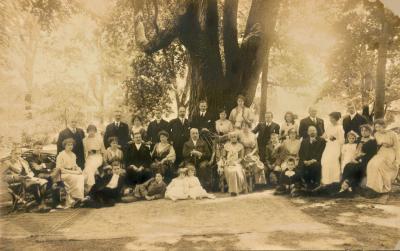 Famille nombreuse de différentes générations posant à l'extérieur devant un gros arbre
