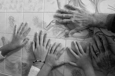 Photo en noir et blanc montrant les mains d'un grand-père et de deux de ses petits-enfants qui sont appuyées sur un mur en plan rapproché.