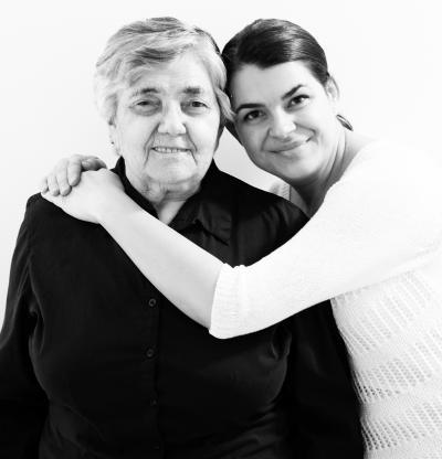 Photo en noir et blanc montrant une grand-mère et sa petite-fille qui l'enlace en plan rapproché.