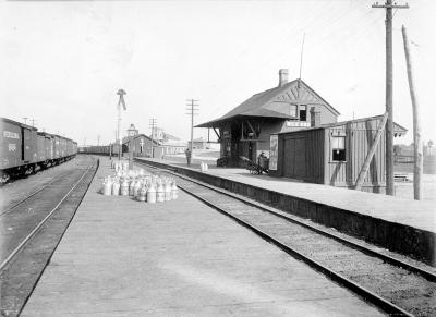 Photo en noir et blanc d'une très petite gare bordée par deux voies ferrées.