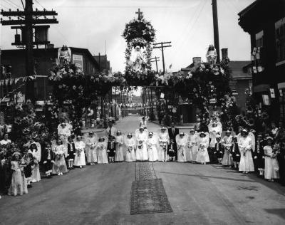 Réunies sous l'arche fleurie, des fillettes aux atours angéliques côtoient de jeunes garçons habillés en petit page pour la procession de la Fête-Dieu