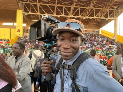 Photo d'un homme tenant une caméra dans une grand salle avec des gradins remplis à l'arrière