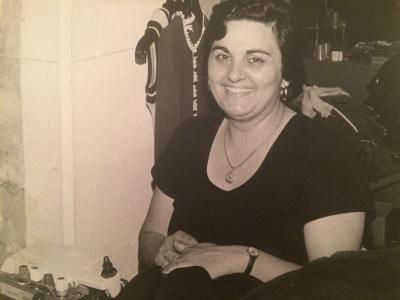 Femme assise et souriante devant une machine à coudre