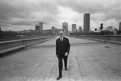 Jean Drapeau marche sur ce qui deviendra l'autoroute Bonaventure. On voit la ville derrière lui.