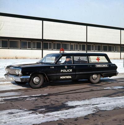 Photographie couleur d'une ambulance noire. Sur la porte du côté conducteur, les mots police et Montréal sont écrits en majuscules. Du même côté, à l'arrière, il y a le mot ambulance. Un gyrophare rouge est visible sur le toit de la voiture.
