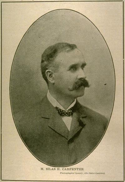 Photographie sépia, dans un médaillon, d'un homme blanc en complet et portant une moustache, sur un fond clair.