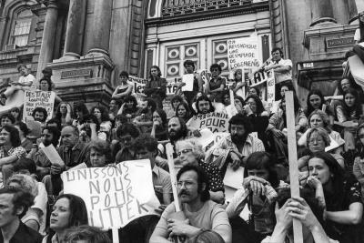 Une cinquantaine de personnes sont assisses sur les escaliers devant l'hôtel de ville de Montréal, pancartes à la main.