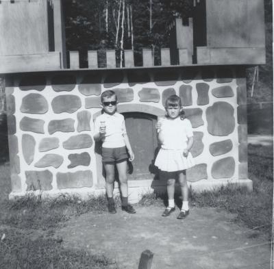 Deux enfants tenant chacun un cornet de crème glacée prennent la pose