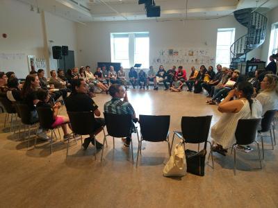 Une trentaine de personnes sont assises sur des chaises en cercle dans une grande salle.