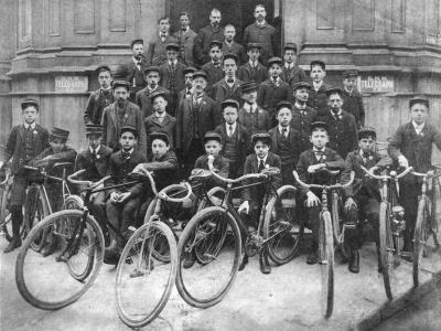 Environ 35 hommes et garçons en rangée posent devant un édifice, avec des vélos en avant-plan.