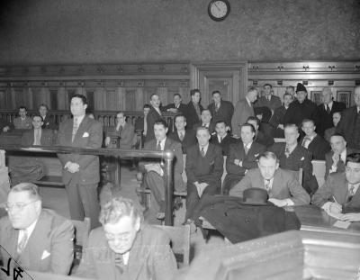 Salle de tribunal remplie d'hommes. À gauche, un homme en complet cravate se tient debout derrière une balustrade. Il a les mains croisées devant lui.