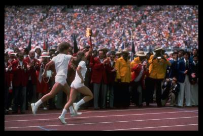 Photographie des deux relayeurs, vêtus de blanc, qui courent sur la piste en tenant la torche olympique.