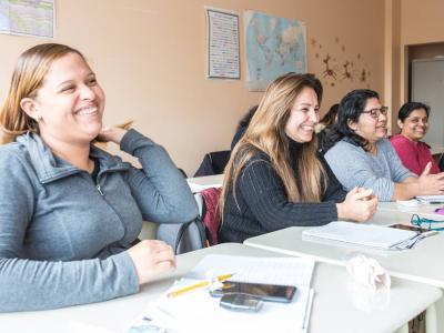Quatre femmes souriantes sont assises à des tables dans une classe.