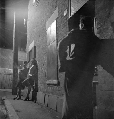 Deux femmes sont appuyées sur un mur de brique et sont éclairées par la lumière d'un lampadaire électrique. Un homme, de dos, les regarde.