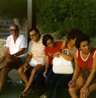 Trois femmes et deux hommes assis sur un banc, souriant