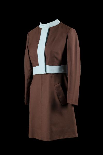 Robe et veste constituant l'uniforme d'une hôtesse du Québec ayant appartenu à Monique Michaud. Costume brun aux accents bleu pâle dessiné par Serge & Réal.