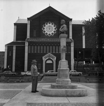 Un homme se tient debout devant la statue de Dante au square Dante, avec l'église Notre-Dame-de-la-Défense à l'arrière-plan