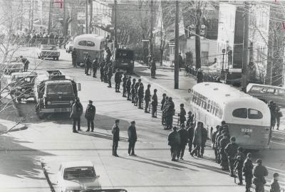 Des soldats bouclent une rue. On aperçoit deux autobus et des voitures.