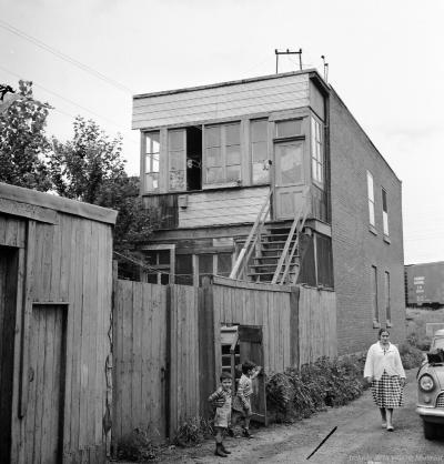 Une femme et deux enfants sur le côté d'une maison rue Britannia.