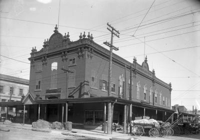 Photo en noir et blanc d'un marché public avec des charrettes sur le côté de l'édifice.