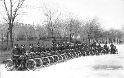 Photographie en noir et blanc d'un groupe de policiers sur leur moto. Ils sont les uns à côté des autres sur le bord de la rue.