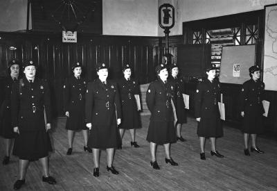 Photographie en noir et blanc d'un groupe de femmes en uniforme dans une salle lambrissée.