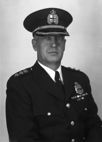 Photographie en noir et blanc d'un homme en plan rapproché taille qui est vêtu d'un uniforme de policier.