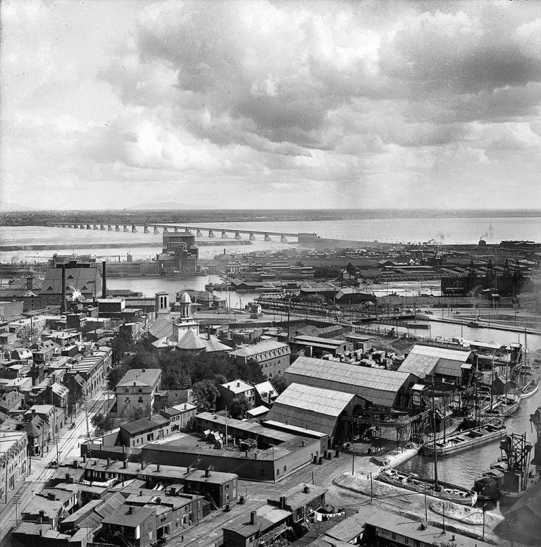 Vue aérienne de Griffintown à la fin du XIXe siècle avec l'église Sainte-Anne, le canal de Lachine et le pont Victoria en arrière-plan