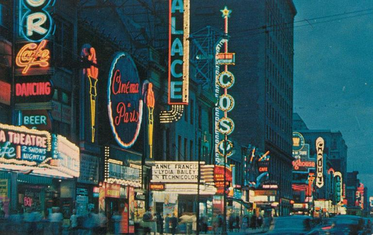 Vue de nuit des façade des magasins de la rue Sainte-Catherine avec les enseignes lumineuses