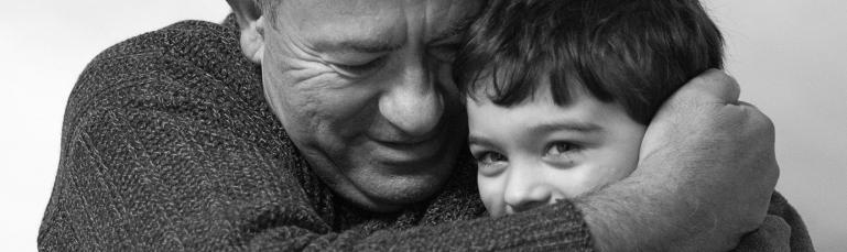 Photo en noir et blanc montrant un grand-père enlaçant son petit-fils en plan rapproché.