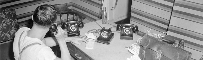 Un homme en tenue décontractée est assis derrière un bureau sur lequel il y a trois téléphones. L'homme utilise celui du centre.