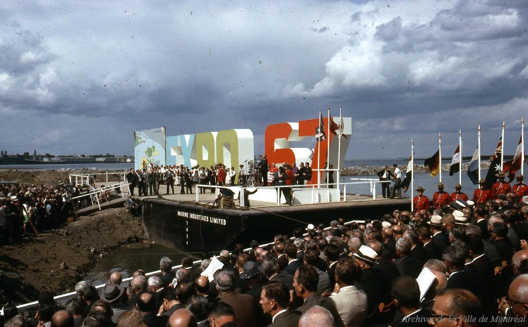 Site de la cérémonie du début de la construction. On voit les lettres Expo 67 et une foule assise.