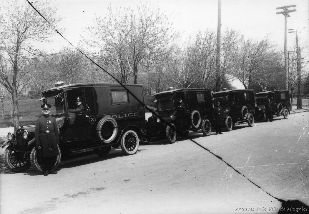 Photographie en noir et blanc où on voit des camions de type fourgon cellulaire avec le mot police inscrit sur le côté. Un policier se tient devant la rangée de véhicules.