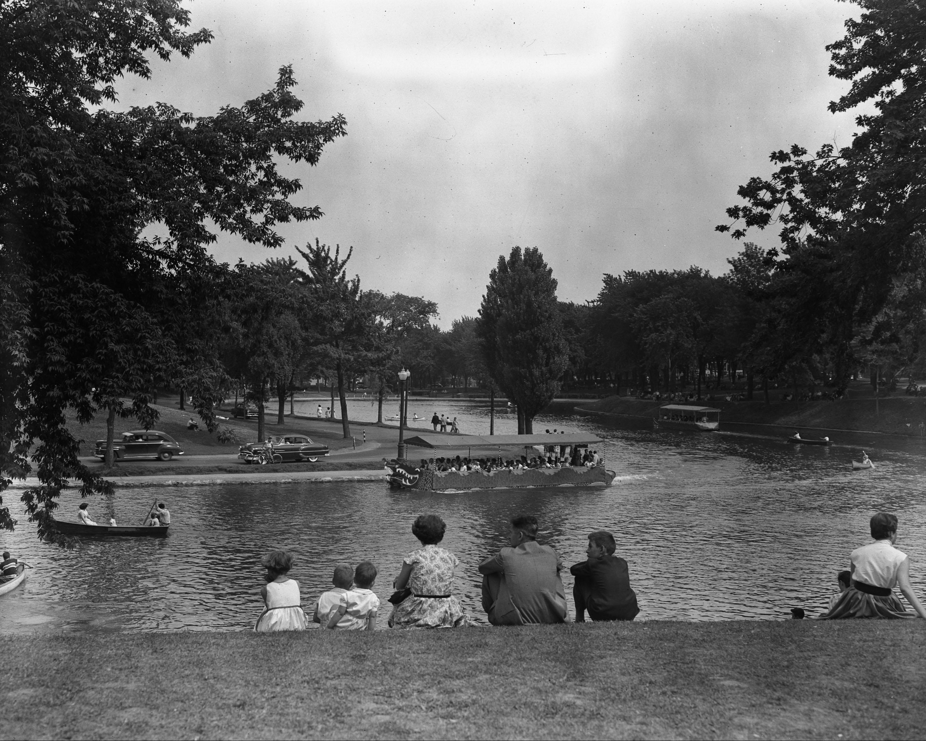 Photographie de promeneurs dans le parc La Fontaine.. L'étang est situé au centre.