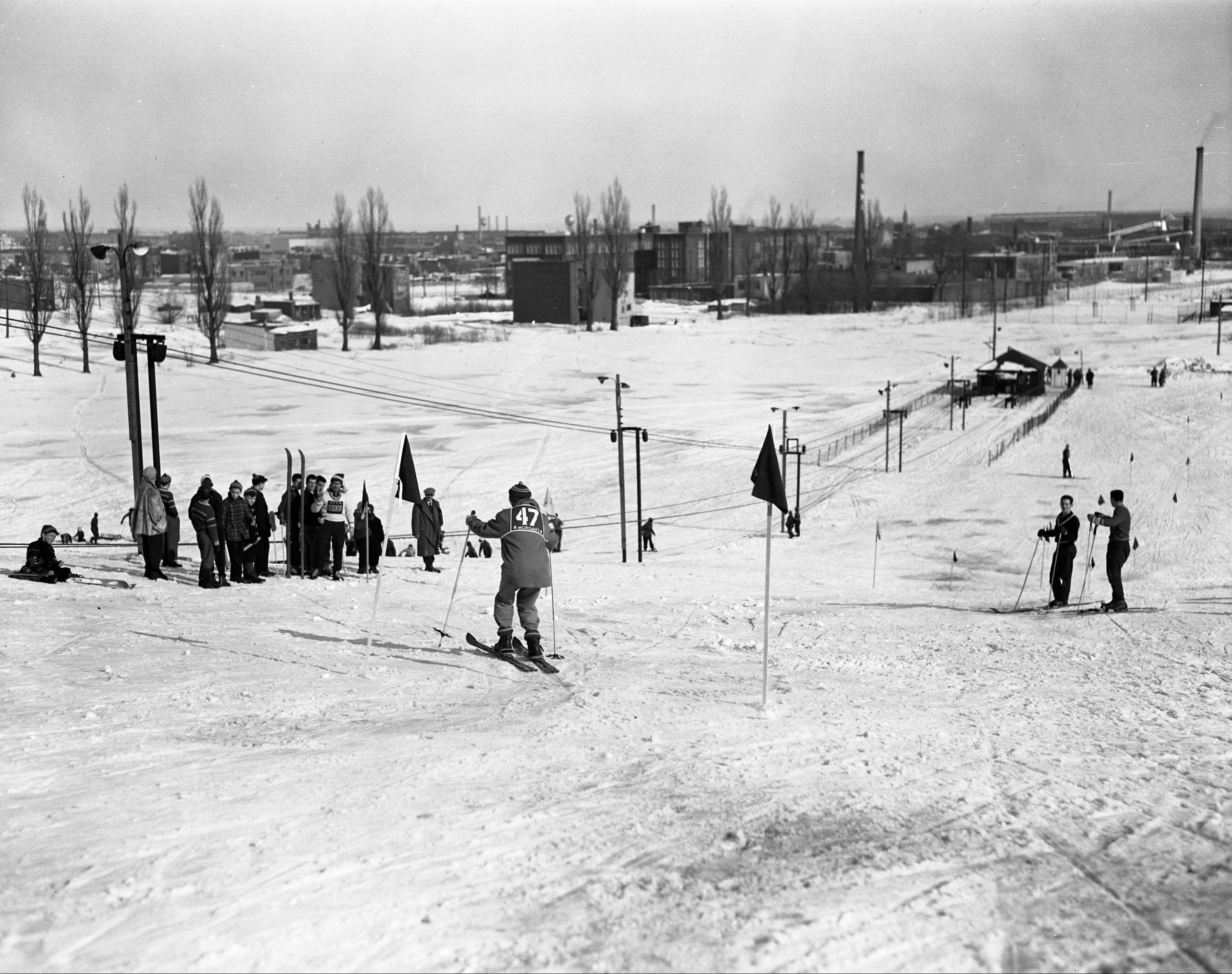 Un skieur portant le numéro 47 est sur le point de descendre une piste. On voit une douzaine de personnes le long de la piste et des édifices en arrière-plan.