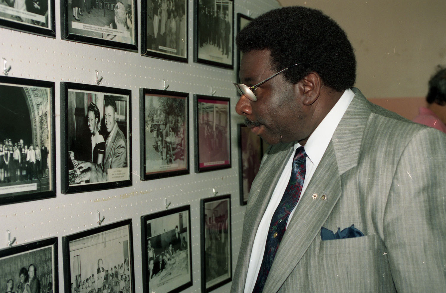 Le pianiste jazz Oliver Jones regardant un mur de photos encadrées au Negro Community Centre