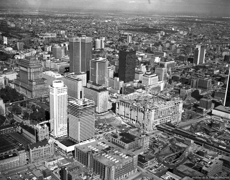 Photographie en noir et blanc du panorama montréalais d'un point de vue surélevé. On reconnaît de gauche à droite : l'édifice de la Sun Life, la Place Ville Marie et le siège social d'Hydro-Québec.