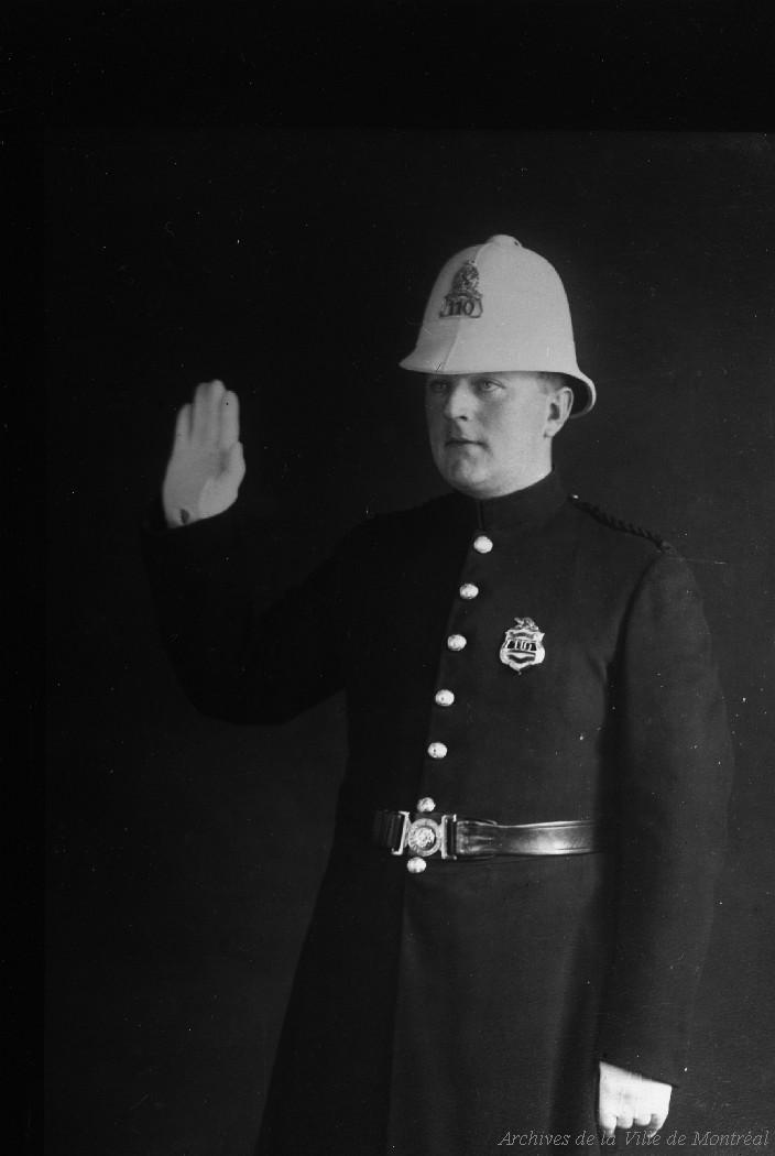 Photographie en noir et blanc d'un policier en uniforme. Il a la main droite levée et porte un couvre-chef blanc de forme un peu conique.