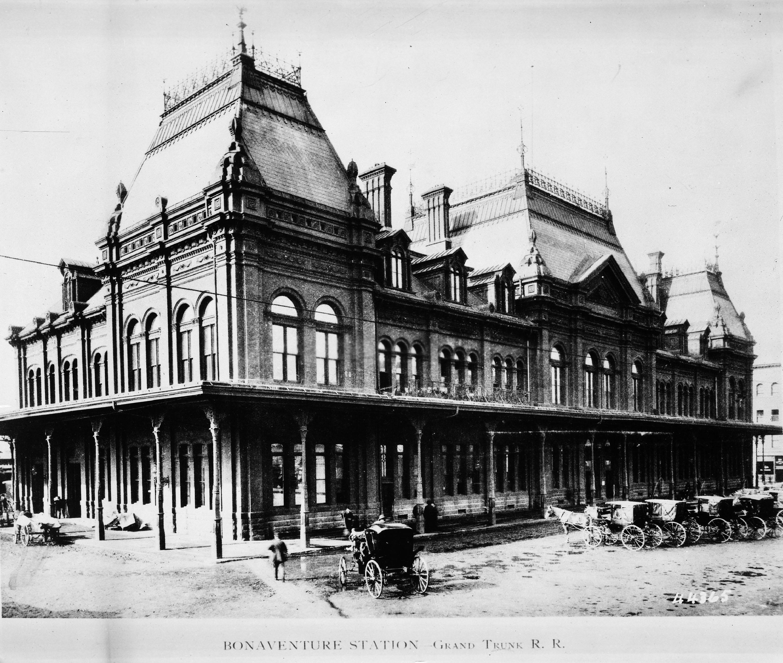Photo ancienne d'une gare avec voitures à chevaux.