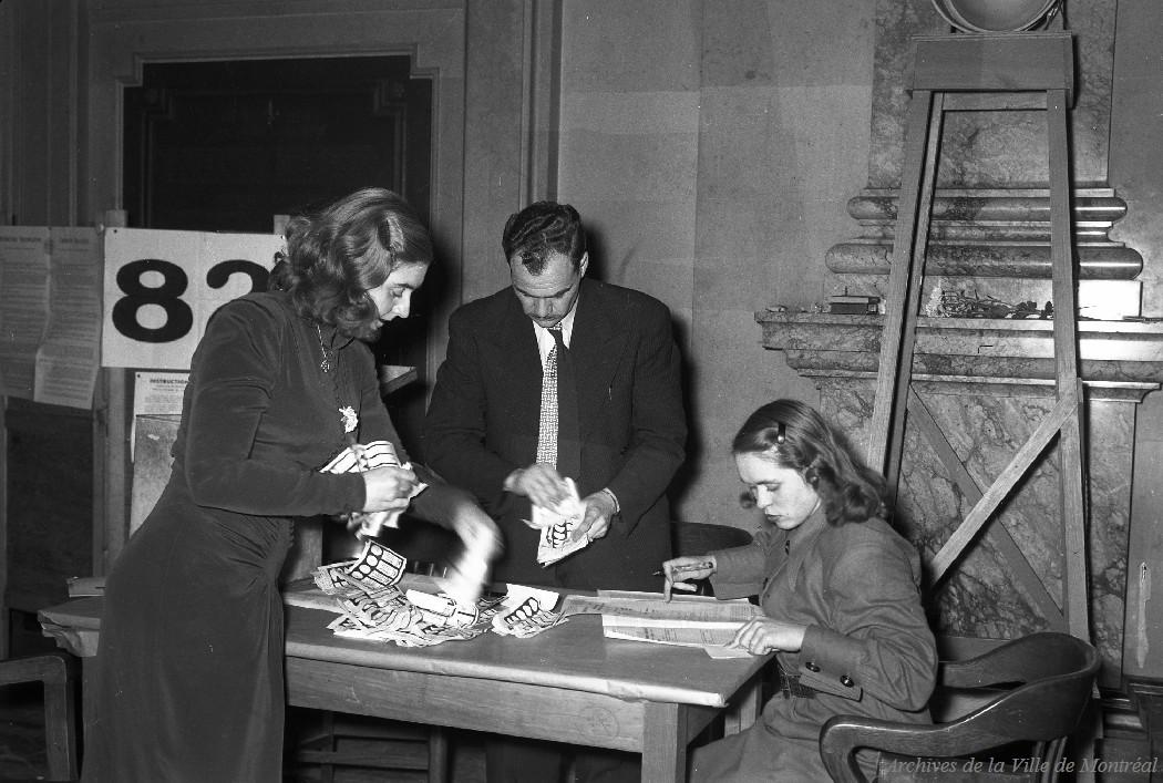 Photographie de trois personnes employées au dépouillement des votes du bureau de scrutin no 82 dans le hall d'honneur.