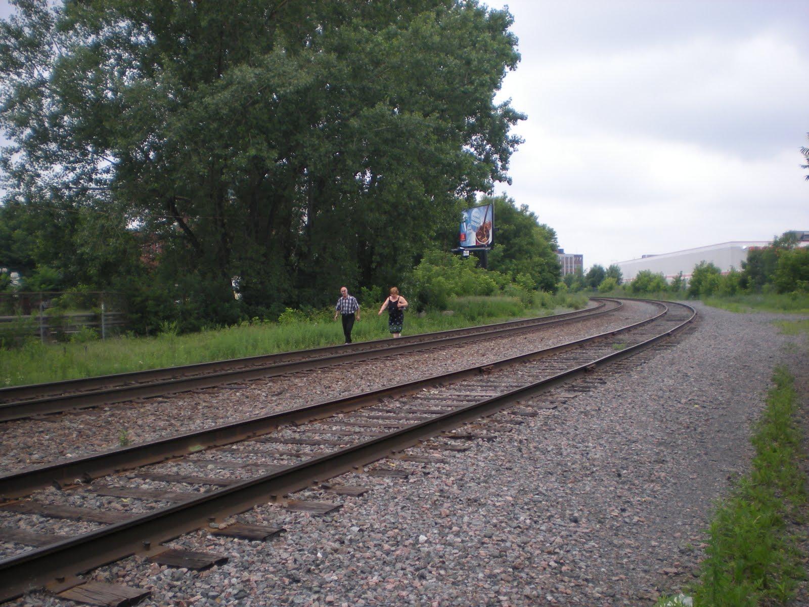 Photo contemporaine d'une voie ferrée double avec un homme et une femme marchant à côté.