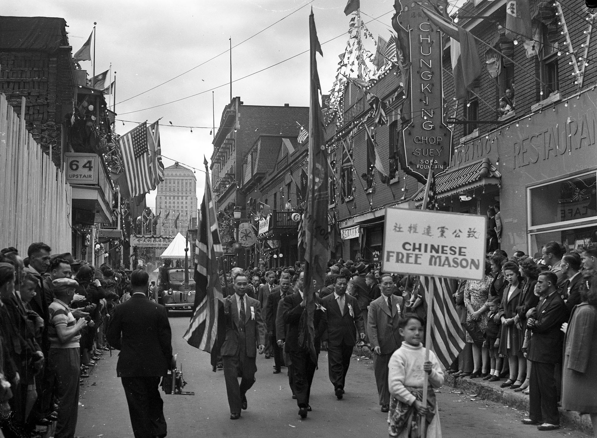 Le 2 septembre 1945, le défilé de la Victoire parade sur la rue De La Gauchetière Ouest dans le Chinatown. En avant-plan, un petit garçon porte une pancarte de l'association Chinese Free Mason.