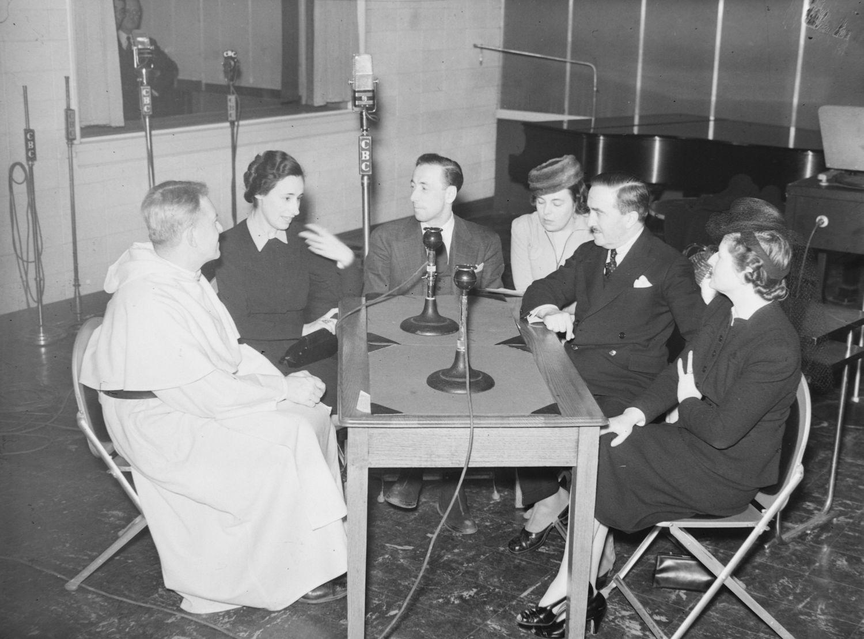 Un groupe de trois femmes et trois hommes assis autour d'une table dans un studio de radio.