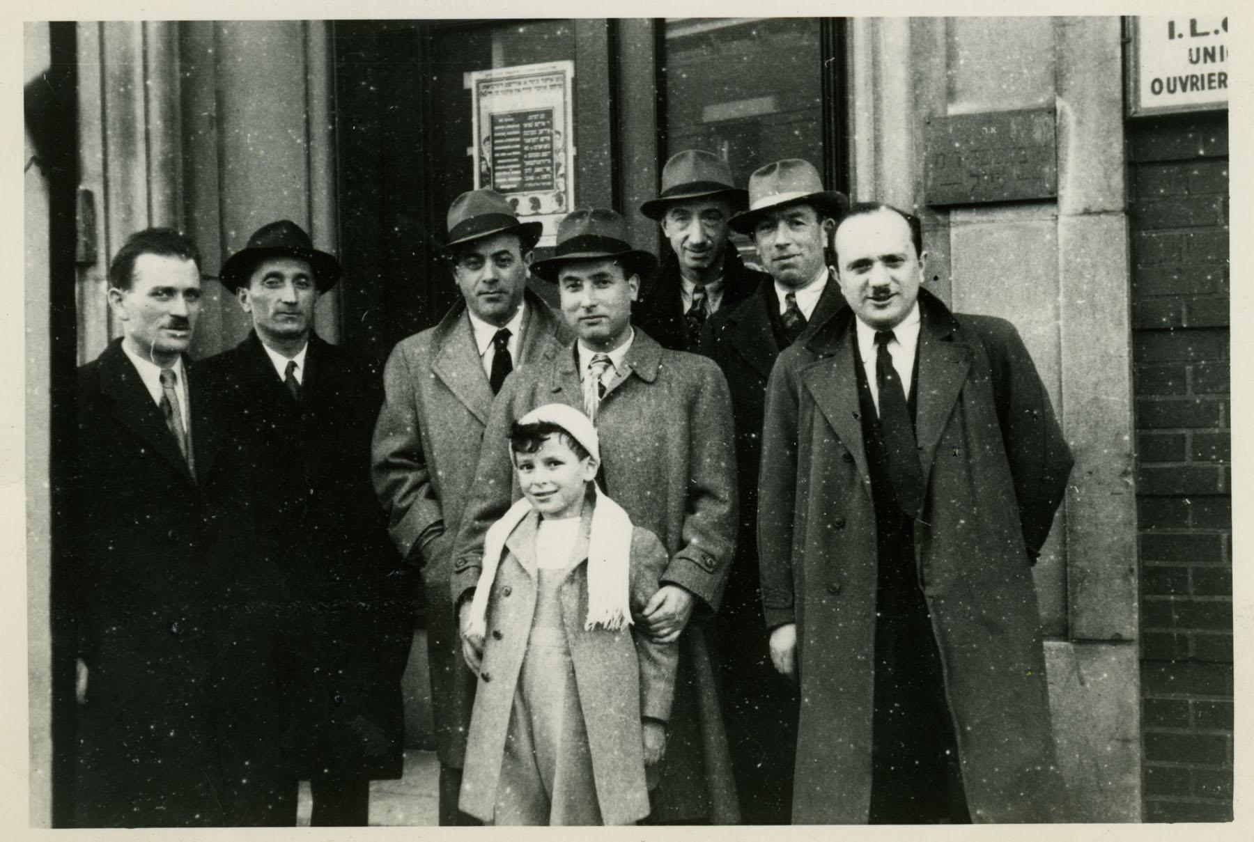 Sept hommes et un enfant à l'extérieur du 4848 boul. Saint-Laurent.
