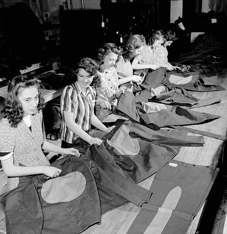 Des ouvrières de l'usine Standard Overalls Company cousent de grands cercles rouges sur les vestons et des bandes rouges sur les pantalons des prisonniers de camp d'internement canadien.