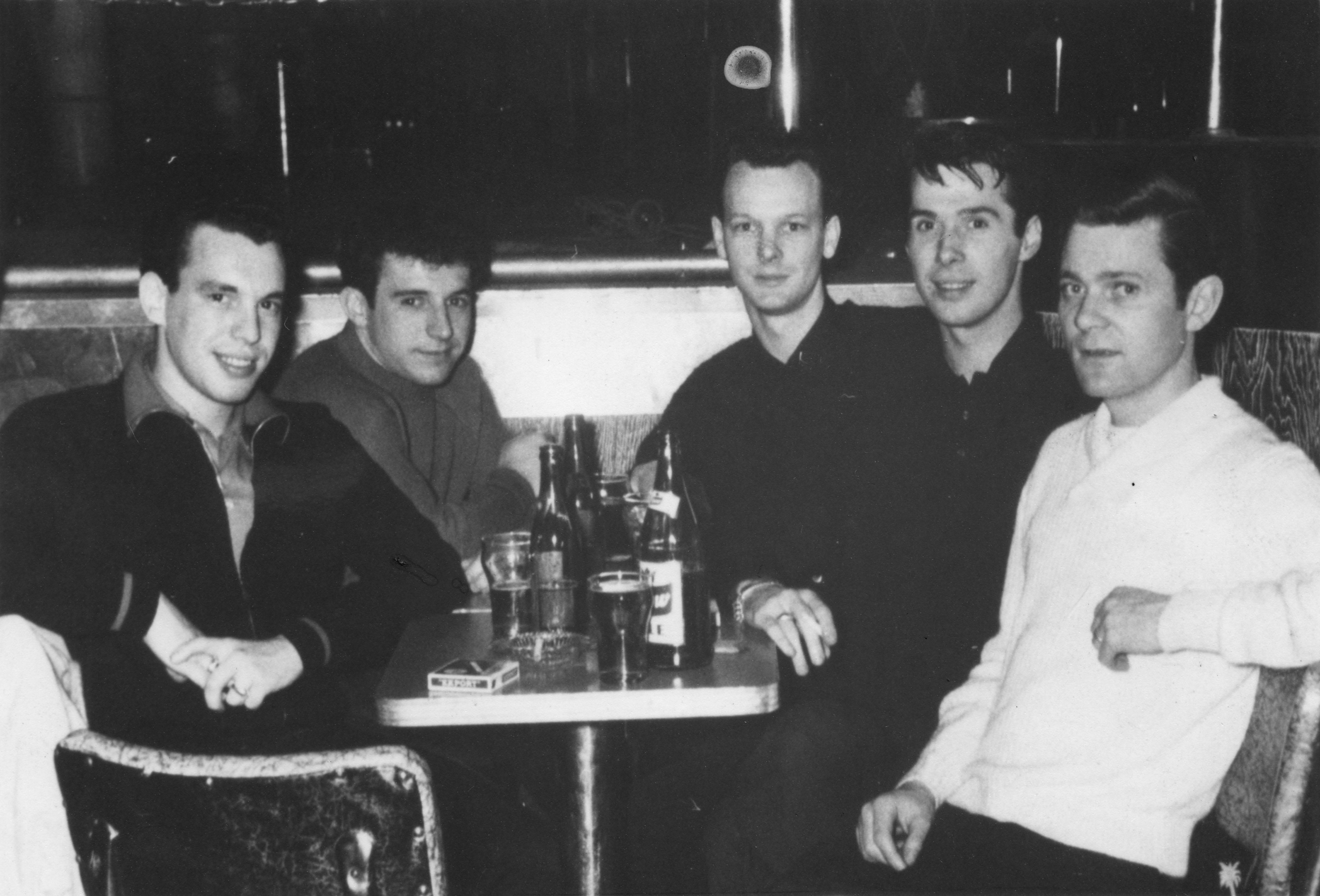 Cinq jeunes hommes sont assis dans un bar autour d'une petite table remplie de bouteilles et de verres.