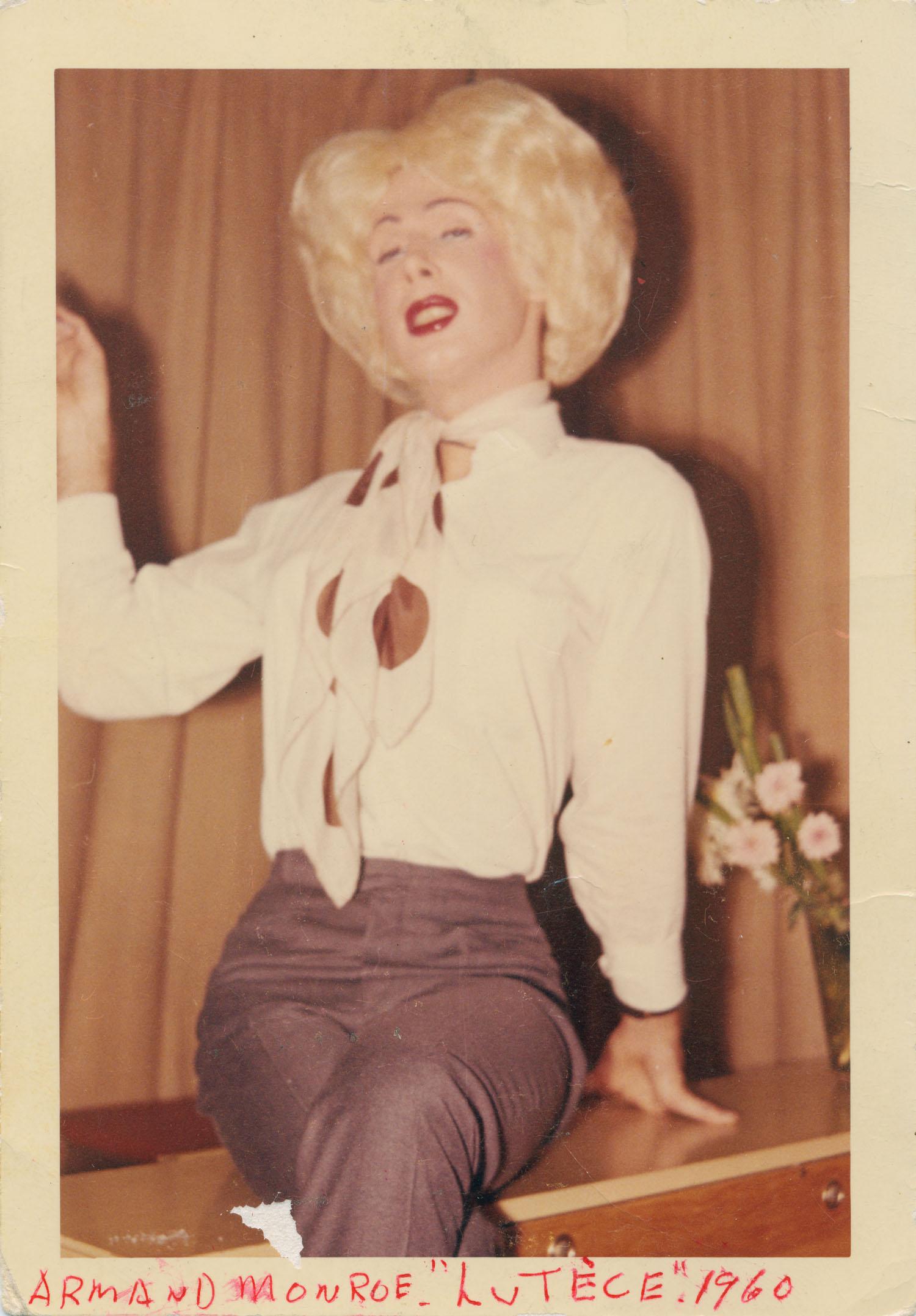 Un homme vêtu en femme arbore une perruque blonde. Il est assis sur un bureau et porte un pantalon bleu et une blouse blanche avec un foulard à gros poids.